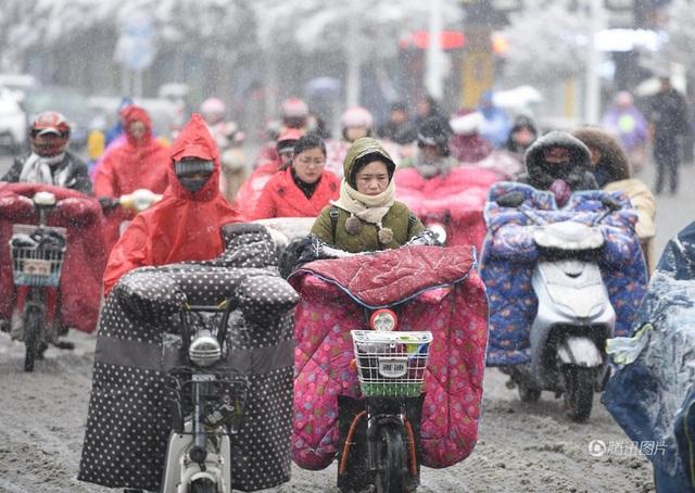 Giá rét cùng với tuyết rơi dày cũng gây nhiều trở ngại cho các sinh hoạt của người dân ở những khu vực bị ảnh hưởng. Trang phục áo khoác dày cùng với bao tay khổ lớn khá phổ biến với những phụ nữ ở đây khi ra đường. (Ảnh: China News)