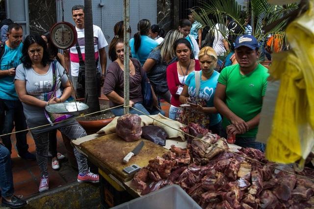 Người dân đứng xếp hàng để mua thịt không rõ nguồn gốc trên đường phố ở thủ đô Caracas. (Nguồn: Wil Riera / Bloomberg)