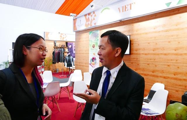 Một đại diện doanh nghiệp Việt Nam tham gia triển lãm tại Hội nghị kết nối kinh doanh và đầu tư ASEAN - Ấn Độ trao đổi với một khách tham quan
