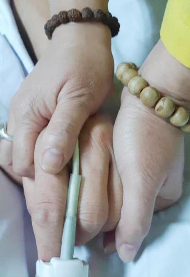 chị Phương nắm chặt tay chồng trước lúc chia lìa.jpg