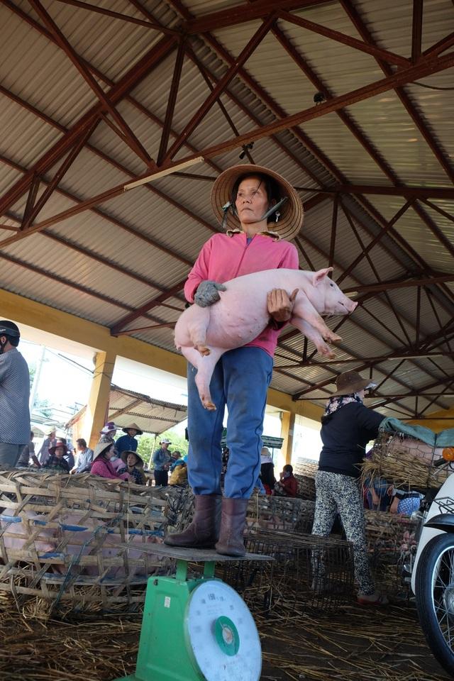 Chị Trần Thị Thảo bồng heo đứng cân. Chị có 30 năm làm nghề bồng heo ở chợ Bà Rén.JPG