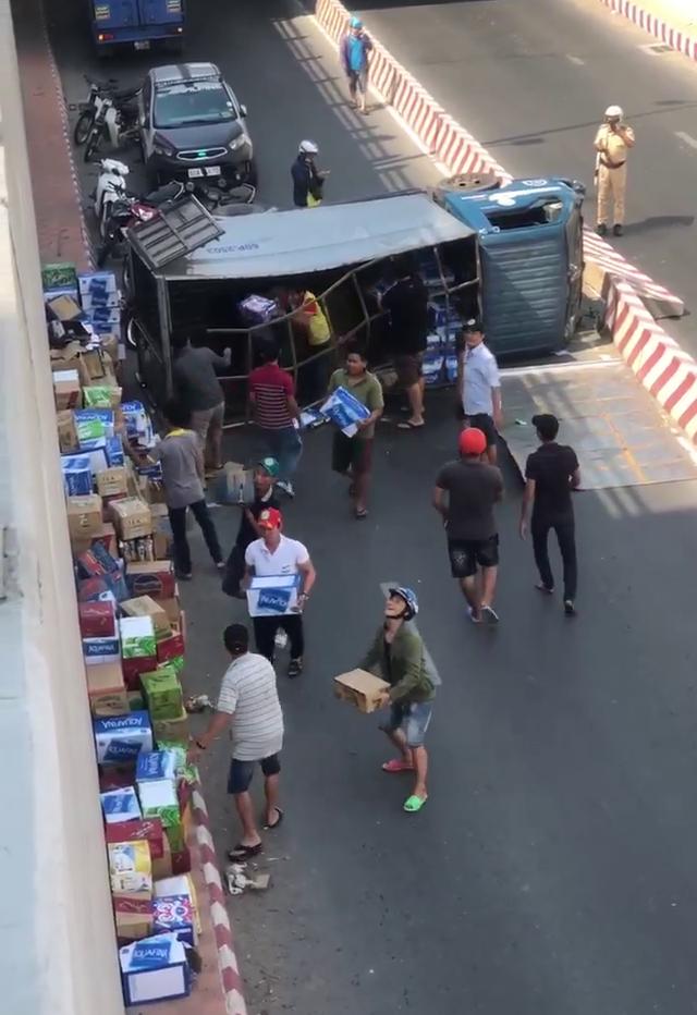 Người dân giúp tài xế gom hàng trăm thùng nước khi xe tải lật - 2