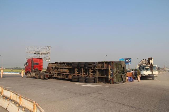 Xe đầu kéo lật nghiêng, hàng chục m3 gỗ đổ tràn trên quốc lộ - 1