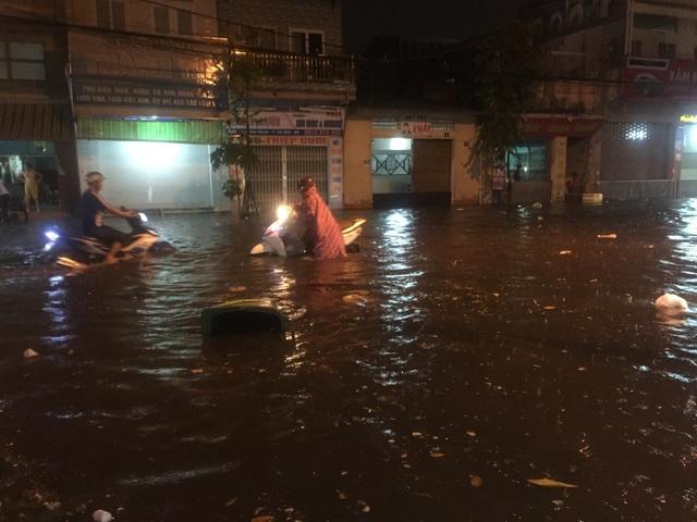 Người dân Biên Hòa bì bõm lội nước sau cơn mưa lớn đầu mùa - 1