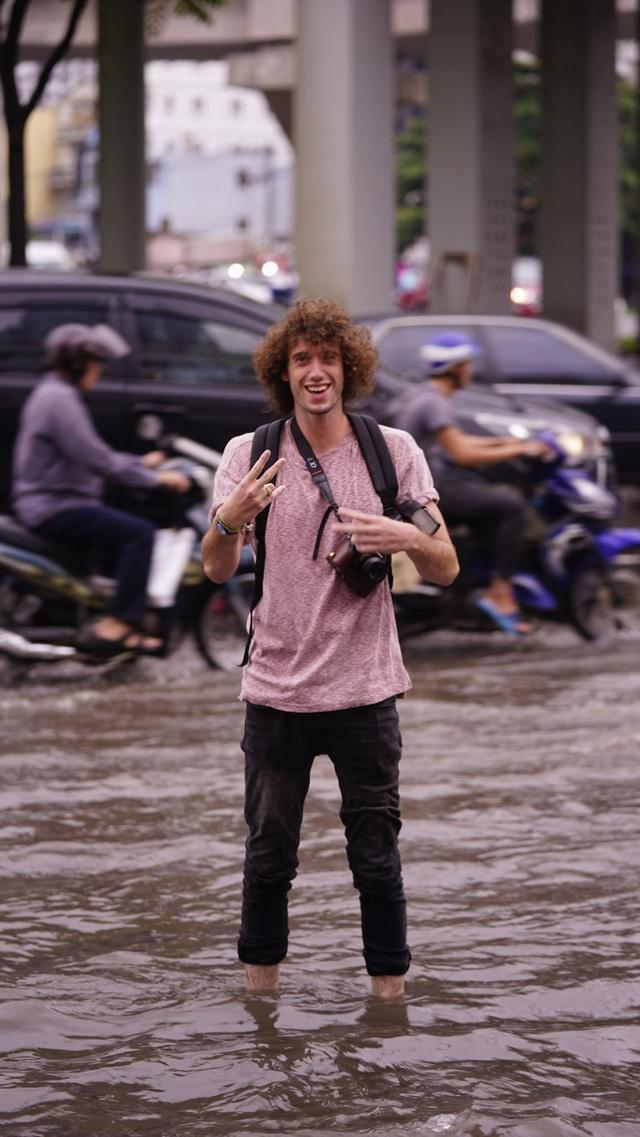 Người dân bì bõm lội nước về nhà sau cơn mưa lớn