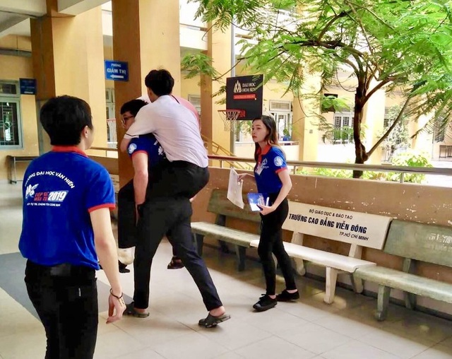 Sinh viên tình nguyện đổi quần dài cho thí sinh để vào làm thủ tục dự thi - 1