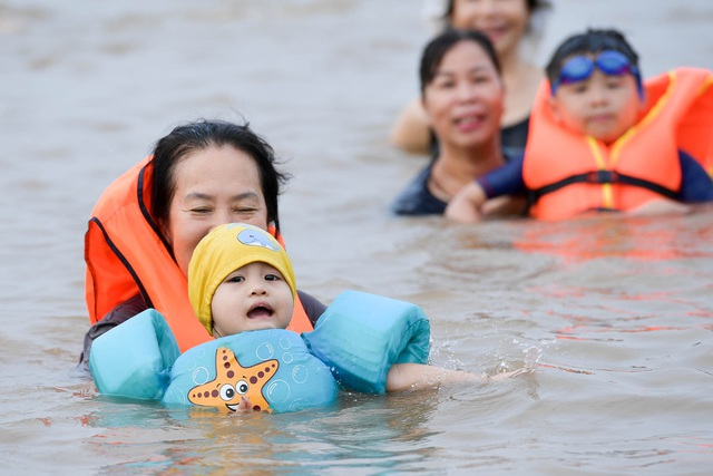 Bất chấp biển cấm, hàng trăm người đổ ra bãi cát ven sông Hồng tắm giải nhiệt  - 7