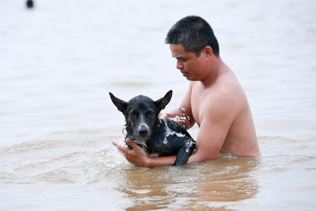 Bất chấp biển cấm, hàng trăm người đổ ra bãi cát ven sông Hồng tắm giải nhiệt  - 12