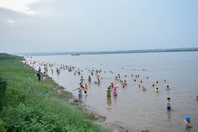 Bất chấp biển cấm, hàng trăm người đổ ra bãi cát ven sông Hồng tắm giải nhiệt  - 1