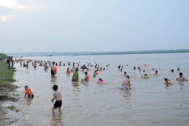 Bất chấp biển cấm, hàng trăm người đổ ra bãi cát ven sông Hồng tắm giải nhiệt  - 13