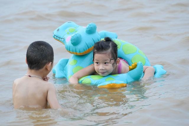 Bất chấp biển cấm, hàng trăm người đổ ra bãi cát ven sông Hồng tắm giải nhiệt  - 9