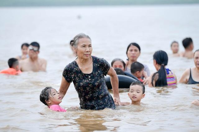 Bất chấp biển cấm, hàng trăm người đổ ra bãi cát ven sông Hồng tắm giải nhiệt  - 10