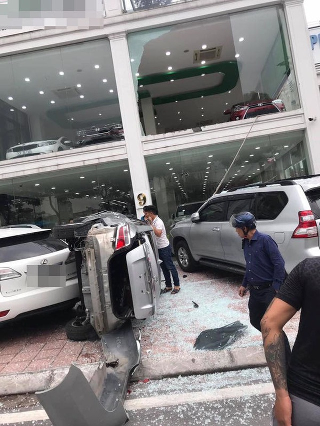 """Hà Nội: Xe Vios """"phi"""" từ tầng 2 showroom xuống đất, đè trúng 1 ô tô khác - 1"""