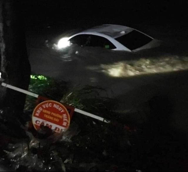 Xe ô tô chở 4 người bị nước lũ cuốn trôi xuống suối - 1