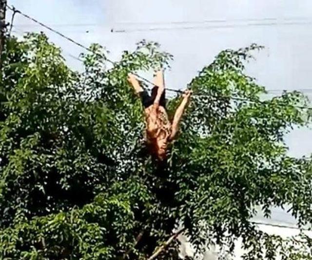 Người dân hoảng hốt khi thấy người phụ nữ đu dây điện - 1