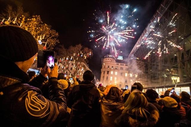 Người dân tập trung xem bắn pháo hoa ngoài trời tại quảng trường Vorosmarty, Budapest, Hungary. (Ảnh: EPA)