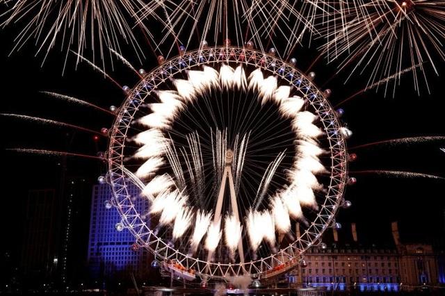 Pháo hoa được bắn từ vòng quay London Eye tại Anh trong đêm giao thừa. (Ảnh: AFP)