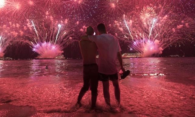 Hai người đàn ông khoác vai nhau ngắm pháo hoa trên bờ biển Copacabana ở Rio de Janeiro, Brazil. (Ảnh: AP)