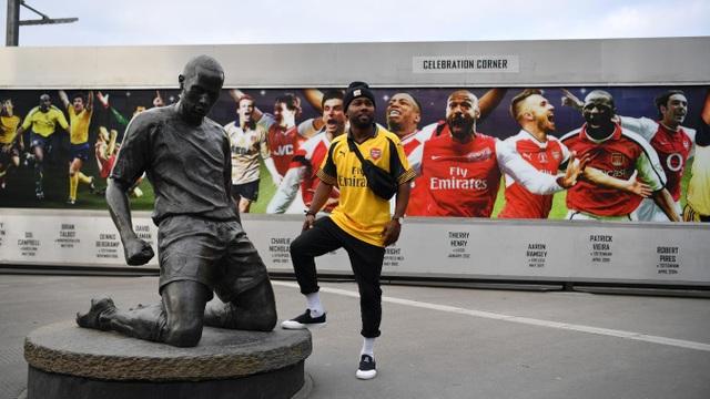 Một cổ động viên Arsenal chụp ảnh bên cạnh tượng của huyền thoại Thiery Henry trước khi vào sân theo dõi trận đấu