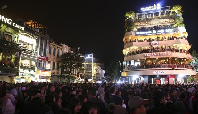 Người dân đổ về quanh bờ hồ Hoàn Kiếm vui chơi và tham dự lễ đón giao thừa mỗi lúc một đông, đến 22h khu vực đài phun nước ở ven hồ Gươm đã kín đặc người.