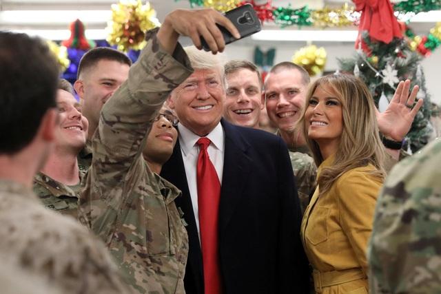 Tổng thống Trump và phu nhân chụp ảnh với các binh sĩ tại căn cứ Al Asad ở Iraq hôm 26/12. (Ảnh: Reuters)