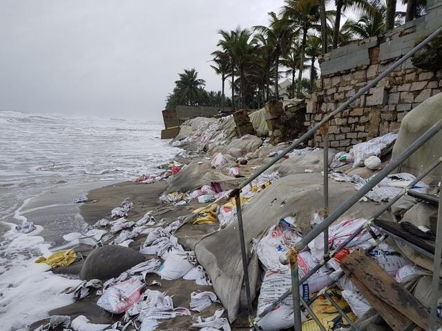 Những bao tải cát lớn nhỏ đều bị sóng đánh tơi tả