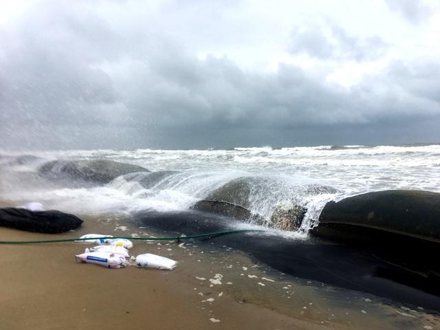 Những con sóng lớn vượt qua những bao tải cát lớn