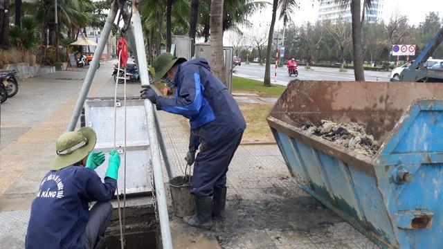 Công nhân múc cát từ cửa xả thải do sóng biển đánh vào.