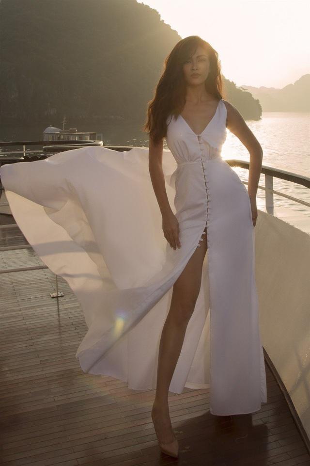 Chiếc đầm trắng giúp Mâu Thủy nổi bật hơn giữa biển xanh. Thiết kế có phần ngực chữ V quyến rũ và hàng cúc điểm xuyến cùng với chân váy xẻ cao, mang đến một phong cách cổ điển, trữ tình cho người đẹp.