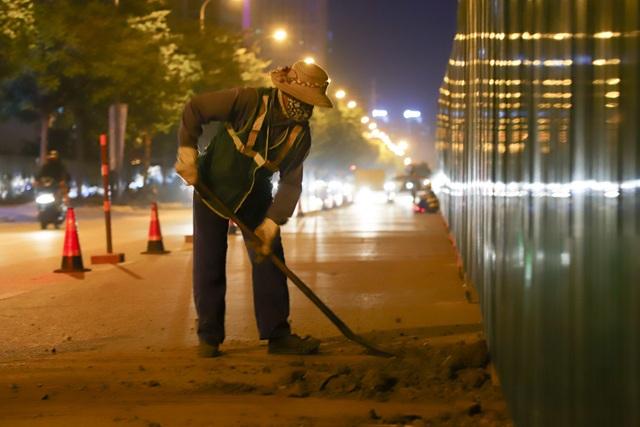 Một công nhân đang dọn dẹp những phần đất thừa trên mặt đường do quá trình thi công để lại.