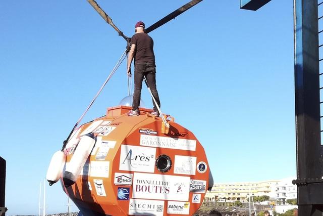 """Người đàn ông Pháp trong ngày """"hạ thủy"""" chiếc thùng màu cam cỡ lớn."""