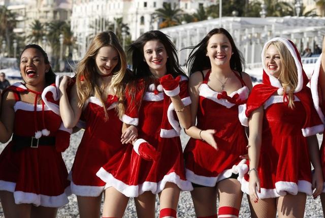Các du khách trẻ trong trang phục Noel đang dạo chơi trên bãi biển ở trung tâm thành phố Nice, Pháp.