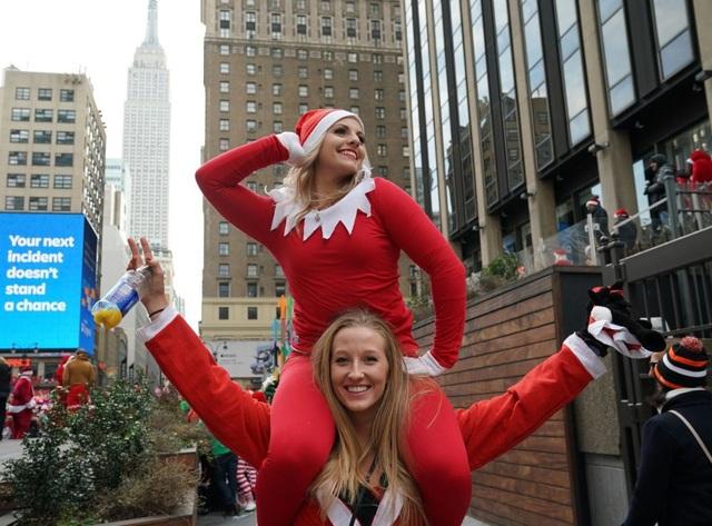 Hai cô gái trong trang phục đỏ rực của ông già Noel, tham dự bữa tiệc trên đường phố ở New York, Mỹ
