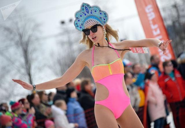 Một nữ du khách trong bộ đồ bơi nóng bỏng, đội mũ truyền thống của người Nga, trượt tuyết giữa ngoài trời hạ xuống âm độ C tại khu nghỉ dưỡng Sochi.