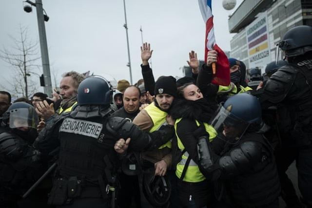 Những người biểu tình thuộc phong trào Áo vàng đụng độ với cảnh sát bên ngoài trụ sở của các đài phát thanh Pháp ở Paris. (Ảnh: AP)