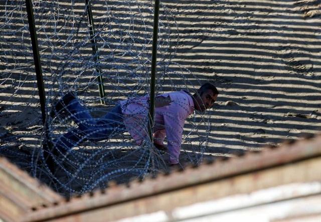 Một người tị nạn nhảy qua hàng rào biên giới và bò qua hàng rào dây thép gai để vượt biên trái phép từ Mexico vào Mỹ. (Ảnh: Reuters)