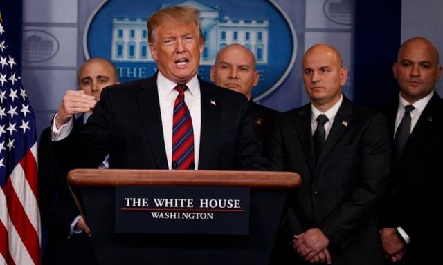 Các thành viên của Cơ quan Tuần tra Biên giới Quốc gia đứng sau Tổng thống Trump trong cuộc họp báo tại Nhà Trắng ở Washington hôm 3/1. (Ảnh: AP)