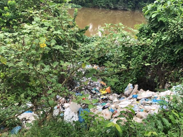 Rác thải được vứt xuống lòng sông phủ kín là mặt nước.