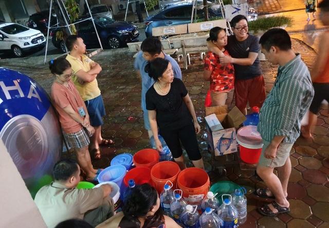 Dân Hà Nội xếp hàng nhiều giờ trong đêm, chờ đong từng chai nước về dùng - 11