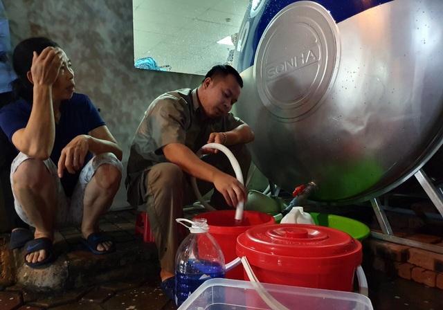 Dân Hà Nội xếp hàng nhiều giờ trong đêm, chờ đong từng chai nước về dùng - 4