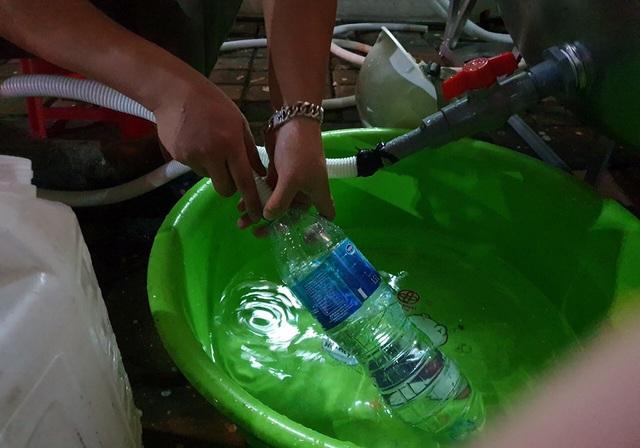 Dân Hà Nội xếp hàng nhiều giờ trong đêm, chờ đong từng chai nước về dùng - 5