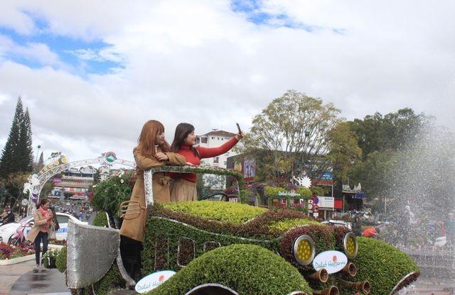 Được đặt ngay đài phun nước giữa Trung tâm TP Đà Lạt, những chiếc xe hoa này khiến nhiều người đi qua phải nán lại check- in.(ảnh: Ngọc Hà)