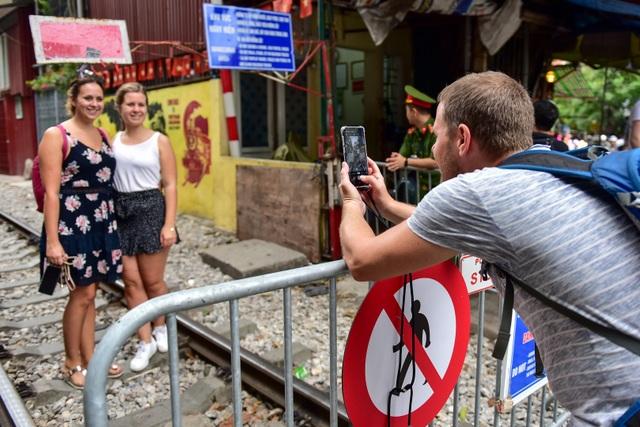 Du khách xếp hàng chụp ảnh phố cà phê đường tàu... qua rào chắn - 1