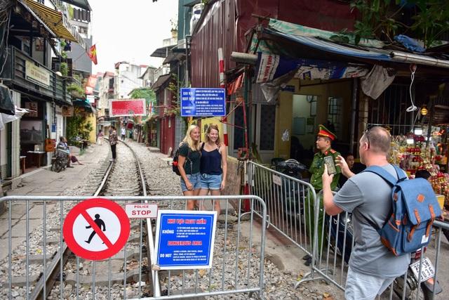 Du khách xếp hàng chụp ảnh phố cà phê đường tàu... qua rào chắn - 9
