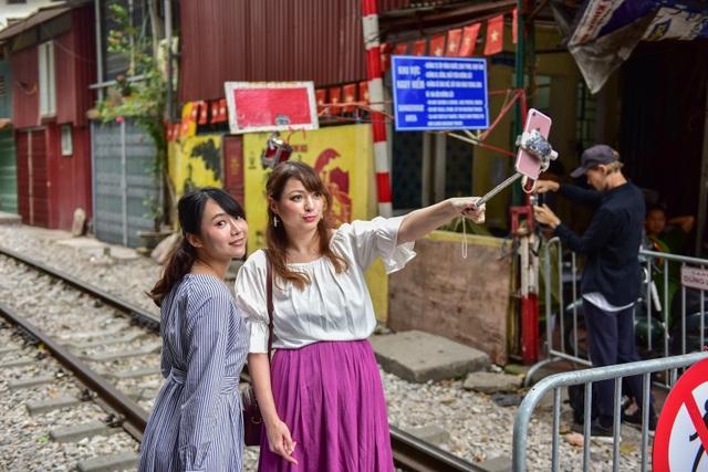 Du khách xếp hàng chụp ảnh phố cà phê đường tàu... qua rào chắn - 3