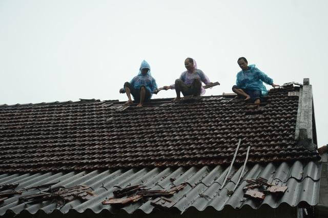 Người dân đội mưa vá mái nhà sau bão - 6