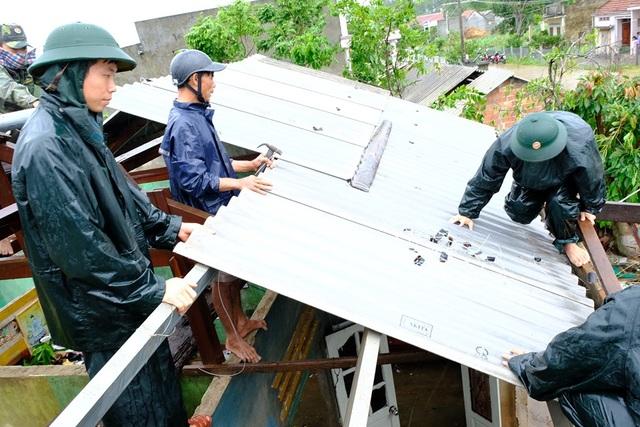 Người dân đội mưa vá mái nhà sau bão - 4