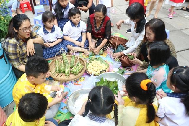 Hàng trăm học sinh tiểu học hào hứng học xay bột, gói bánh tét ăn Tết - 9