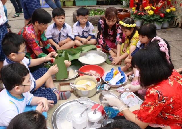 Hàng trăm học sinh tiểu học hào hứng học xay bột, gói bánh tét ăn Tết - 1