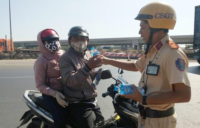 CSGT tặng nước suối, khăn lạnh cho người đi xe máy về quê ăn Tết - 1